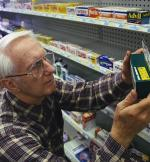 old man looking at a packet pf prescription drugs