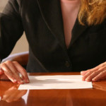 lady sat in boardroom looking to write on piece of paper