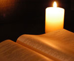 A photo showing a bible and candle