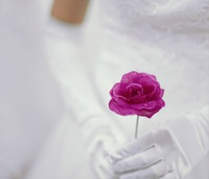 A bride holding a dark pink rose
