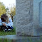 Child weeping near grave