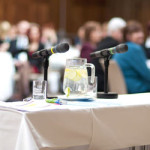 image of conference with microphones on table