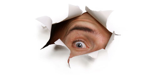 man looking through hole in paper