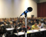 A picture of a microphone infront of a room full of people