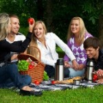 Five happy friends on picnic in a park