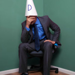 man sat in corner with dunce hat on