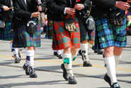 Several people wearing kilts and playing the bagpipes